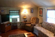 Living room area with recliner, full size couch and flatscreen television. Cable, DVD player and DVD's are provided for your viewing pleasure.