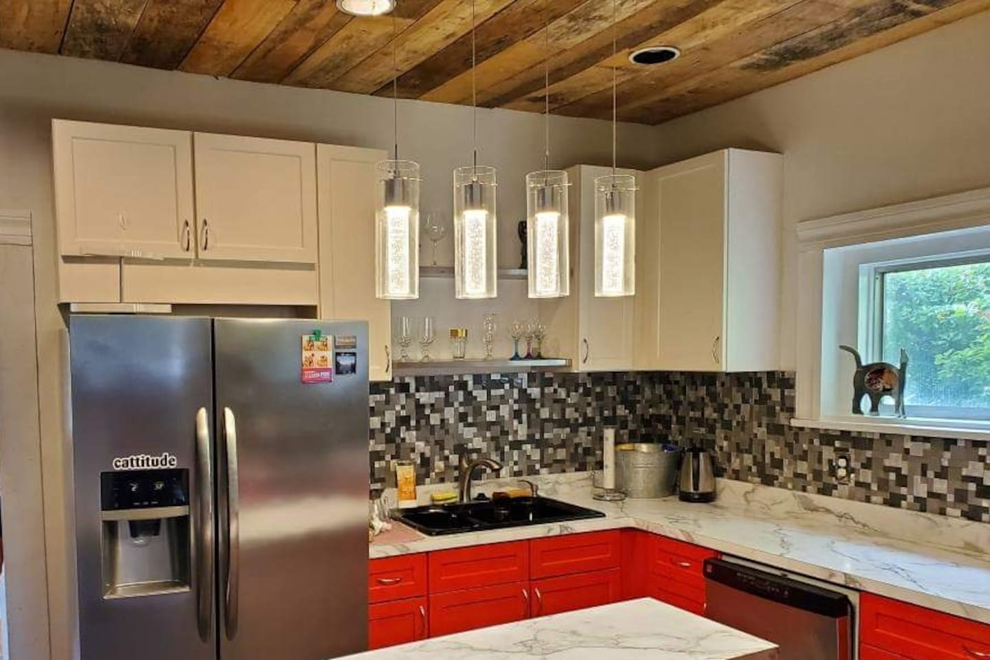 Brand new kitchen featuring stainless steel appliances, a custom wood ceiling, gas stove and rolling island.