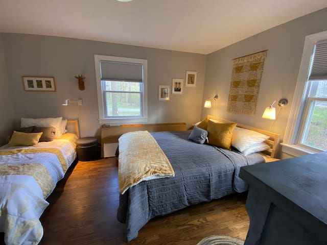 Queen/Twin sleeping in front bedroom. Lighting, tables and plugs for charging are located beside each bed. Bedrooms have light blocking cellular shades.