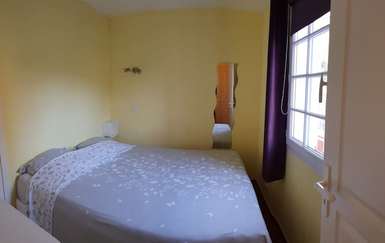 La chambre avec un lit de 160x200, des rideaux occultant et une commode 4 tiroirs
