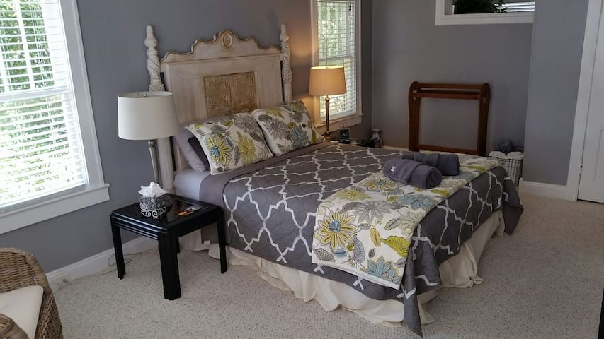 Bedroom with Queen sized bed and seating area.