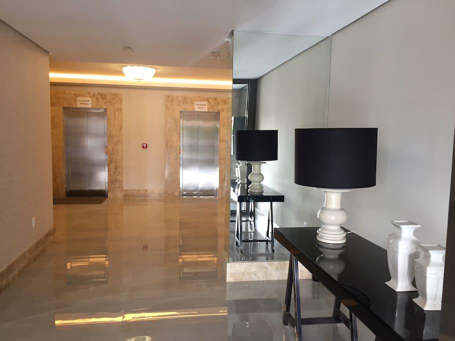 Hall de entrada com elevadores social e serviço