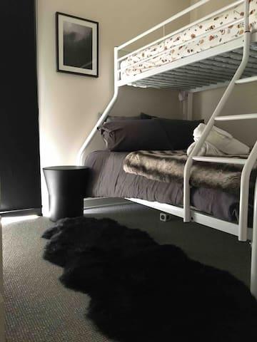 Double & singlebunk beds with bush views, sheepskin rugs, bedroom heater, wardrobe & shelves. Stylish & comfortable .