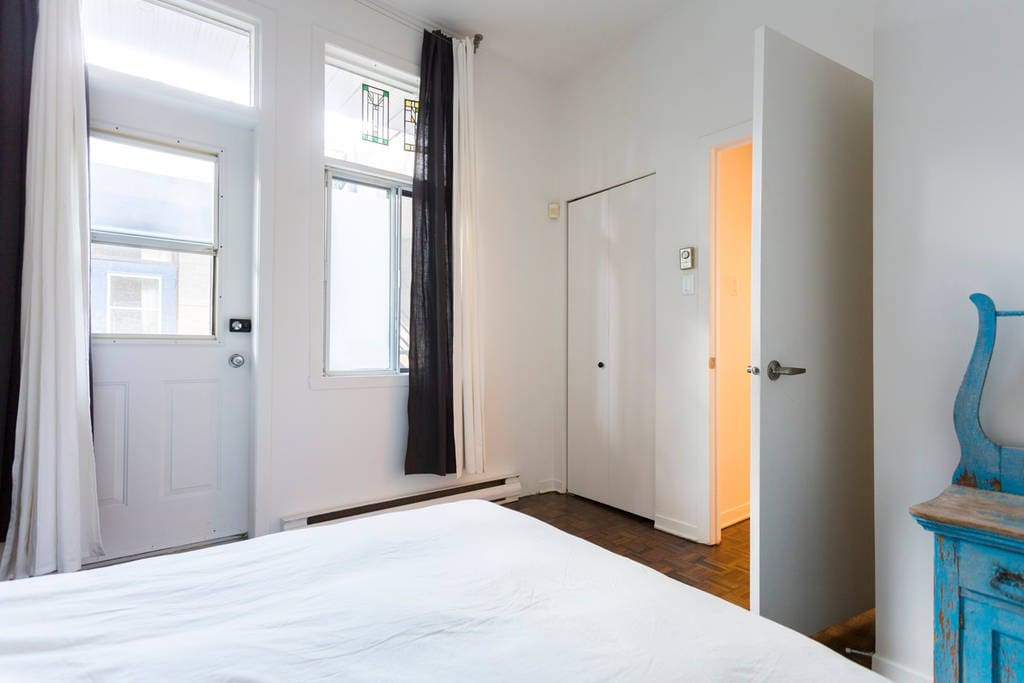 The bedroom has access to a small side balcony overlooking a courtyard