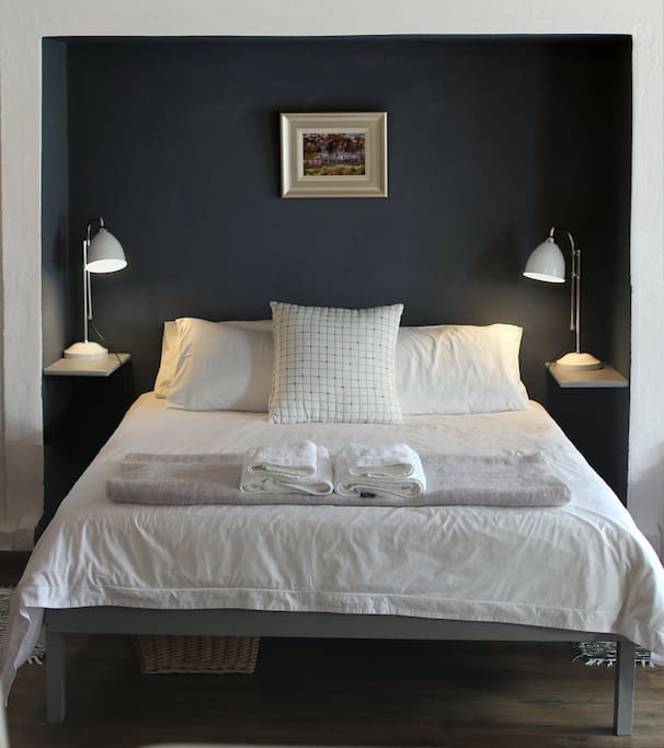 Comfortable queen size bed with crisp white,percale linen and set into a cosy nook.
