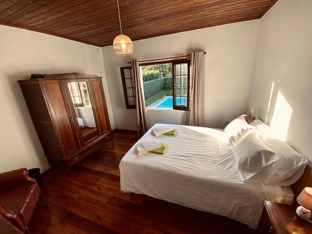 Bedroom in main house with double bed and window that overlooks the pool (complimentary bath & pool/beach towels)