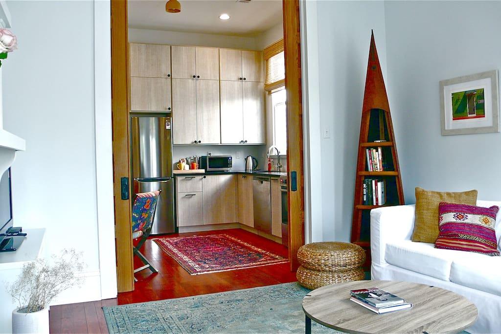 Cypress pocket doors divide living room and full kitchen.