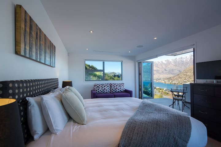 Indulge in a stay in the luxurious master bedroom with a plush king bed and a private, lake-facing outdoor deck