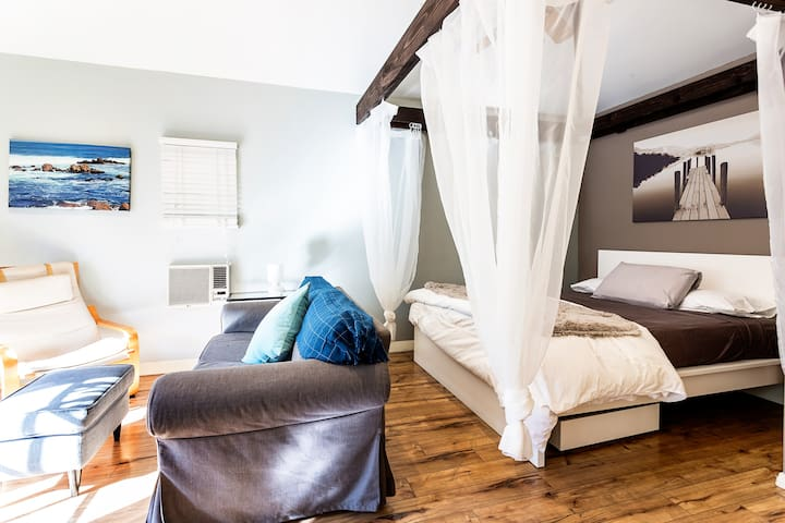 Luxury memory foam bed Queen size bed beneath a rustic, wooden beam and breezy canopy