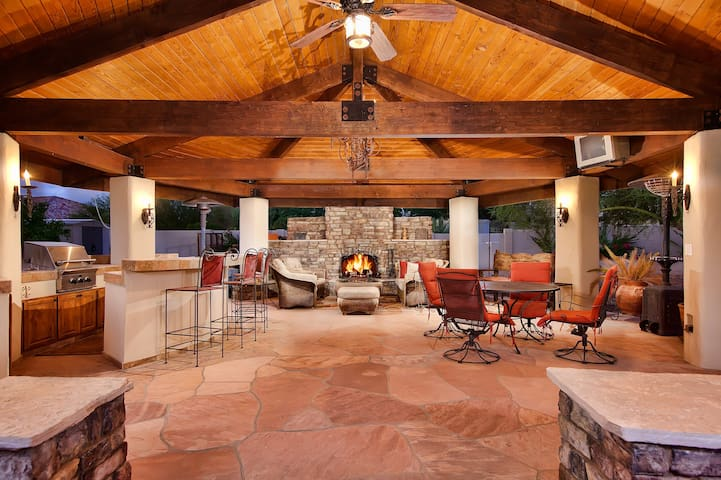 Covered outdoor ramada with fireplace and built-in gas barbecue.