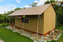 Side of Glamping tent.  Windows on either side with bug mesh.  View from the driveway as you enter the property