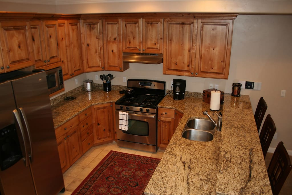 Kitchen with granite countertops, well stocked for cooking