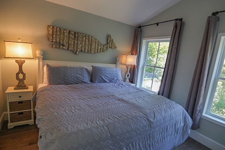 King bed with dual night stands, ceiling fan, and curtains.
