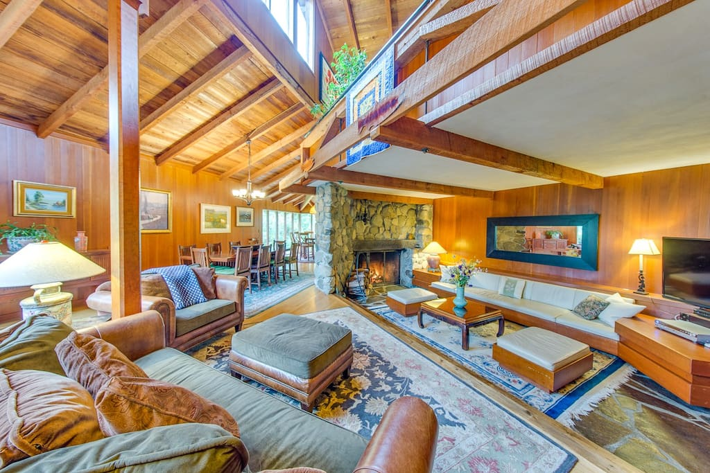 The light-filled Great Room features a sunken area with grand stone fireplace, three couches and opens to the dining and kitchen areas.