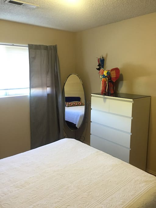 Your bedroom with a full length mirror, natural light, shades and curtains, and dresser.