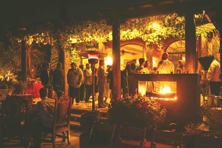 Evening gathering poolside with see through fireplace and heaters