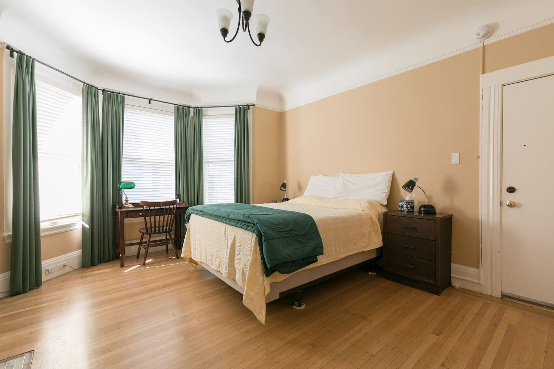 Main room showing premium comfort bed, desk, bay window, nightstand, front door
