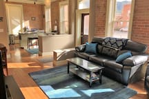 Make yourself at home in the bright and open exposed brick kitchen, dining, and living rooms. Also, the couch doubles as a sofa sleeper.