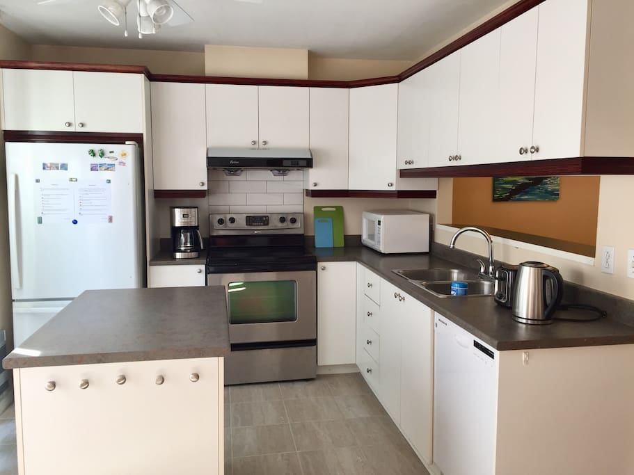 1st floor kitchen with microwave, toaster, coffee maker, pots, dinner sets etc.