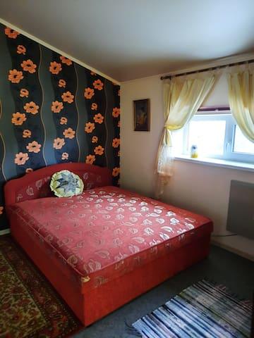 Уютная спальня на втором этаже,  15 м. Кровать кинг-сайз, два комода, шкаф, оригинальный кожаный светильник.  Бра. Картины- вышивки. Окно на юг. Часть западной стены остеклена с выходом на огромный балкон (40м).  Дизайн в стиле арт-деко.
