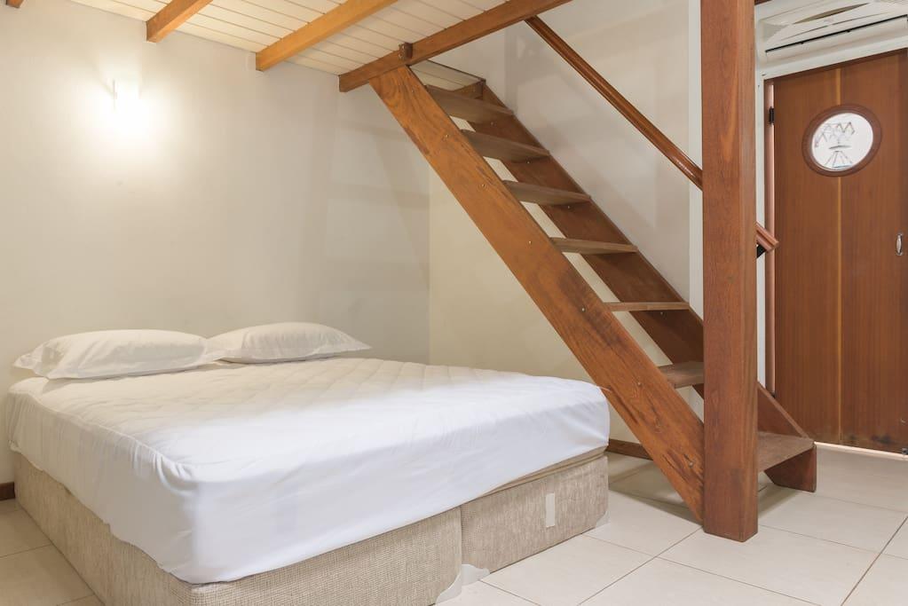 Escada para área superior e porta de uma pequena área de serviço.   Stair to the top loft area and door of the small service area.