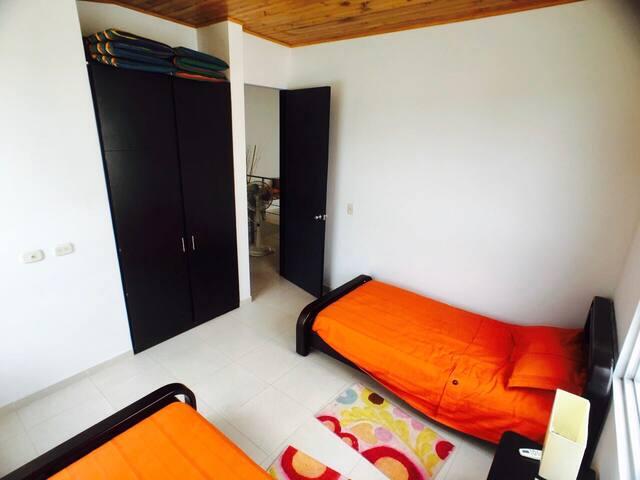 Alcoba 2 con dos camas individuales, closet amplio, mesa de noche y aire acondicionado.