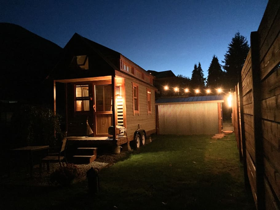 Tiny house at night showing lit entrance path on the right of the photo.