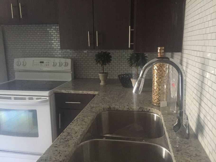 Kitchen                                                       Gorgeous renovated kitchen has granite countertops and glass  tile backsplash.                                                  Full size refrigerator  and microwave                                                                      Keurig Coffee Maker    Coffee sugar creme included                                             Electric stove/oven                                                             Basic dish ware