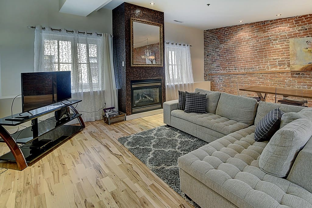 A comfortable living area with large TV, plush carpet and gas fireplace