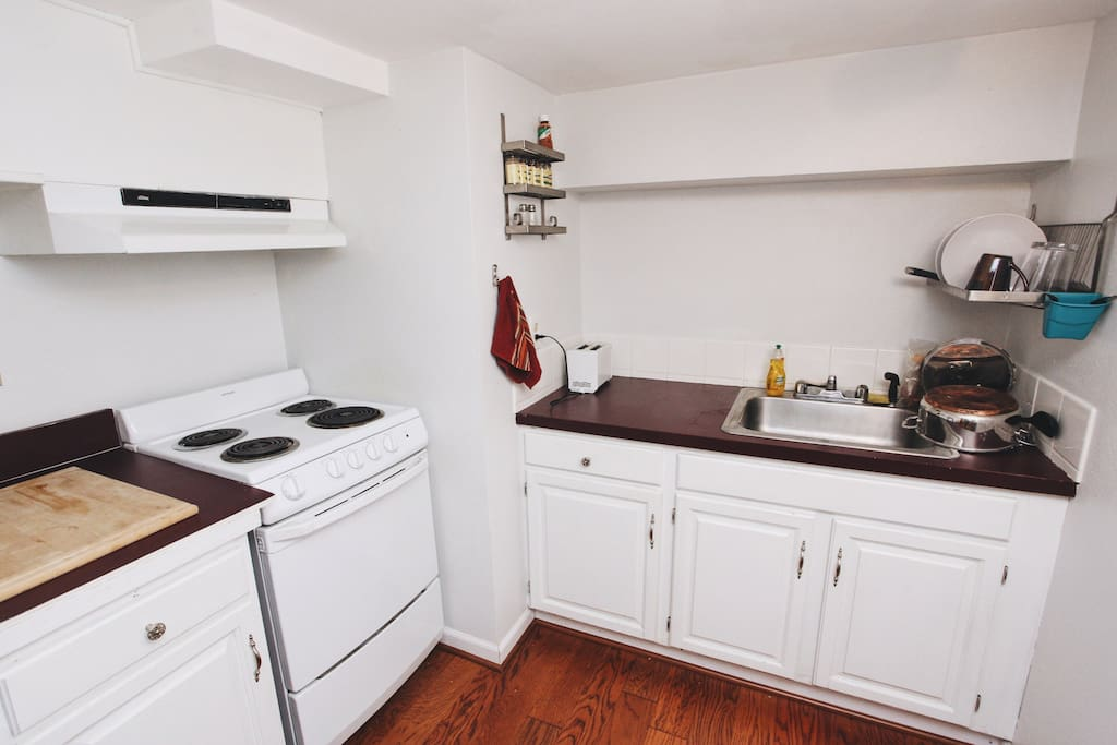 The kitchen is outfitted with a stove, oven, refrigerator, toaster, microwave, and French press.