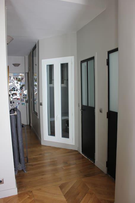 Porte d'entrée au fond et porte-fenêtre blanche du patio. A droite, la première porte noire : WC et la seconde : SDB