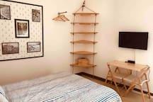 Schlafzimmer mit offenem Kleiderschrank, Tv, Balkon und eigenem Badezimmer