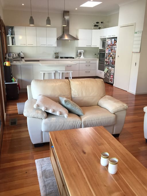 The kitchen opens out onto a TV area with comfy couches. There is a mini kitchen for kids to enjoy practising their cookery skills, and a small table and chairs.