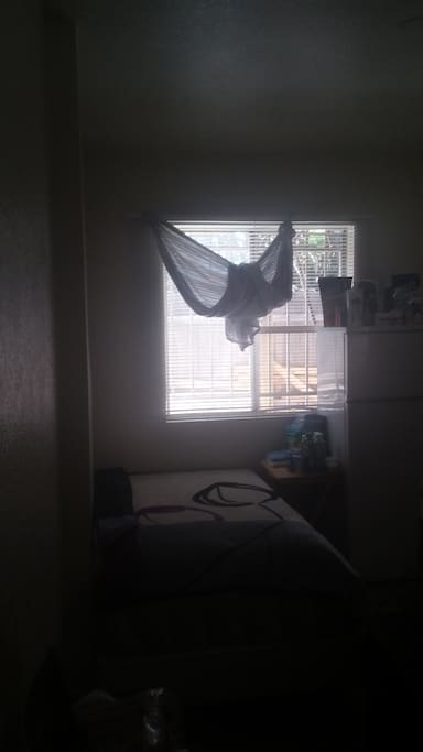 This is the bed next to the window there a little foldable table in the room also .