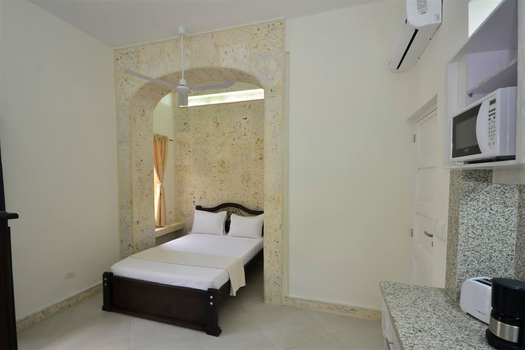 View of bed in travertine archway