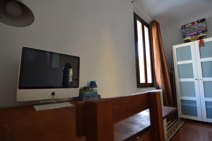 Scrivania con Pc e sedie, finestra su Viale Storchi.