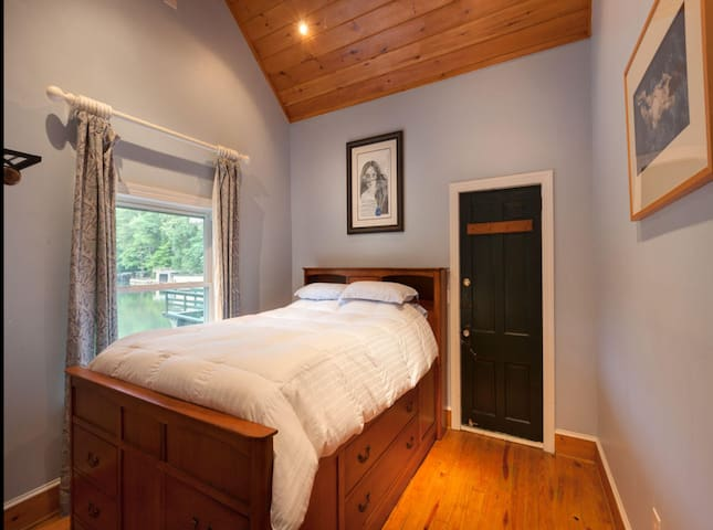 The master bedroom on the second floor which leads to the sunroom. Please note we have changed the position of the bed to face the window so you can watch the lake as you wake up.