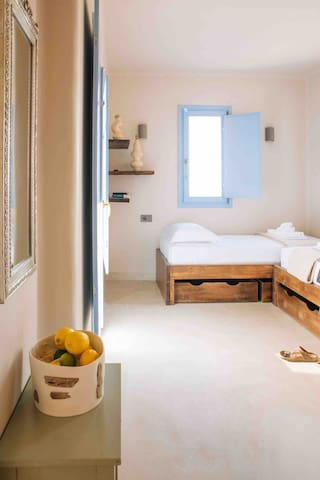 Upstairs open bedroom with two single beds and balcony