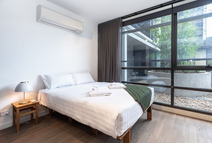 Wake up in a plush queen bed dressed in top-quality linen and gaze out over the rooftop garden through floor-to-ceiling windows