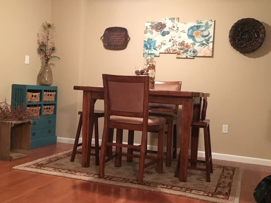 The dining room table has a leaf and more stools for additional seating.