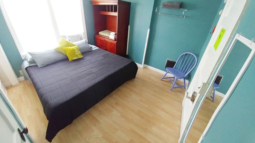 Private room w/ king bed, keycode door, window AC, shelves, closet, chair, towel rack, tissues, wall mirror, first aid. (sheets/blankets/pillows may differ from picture)