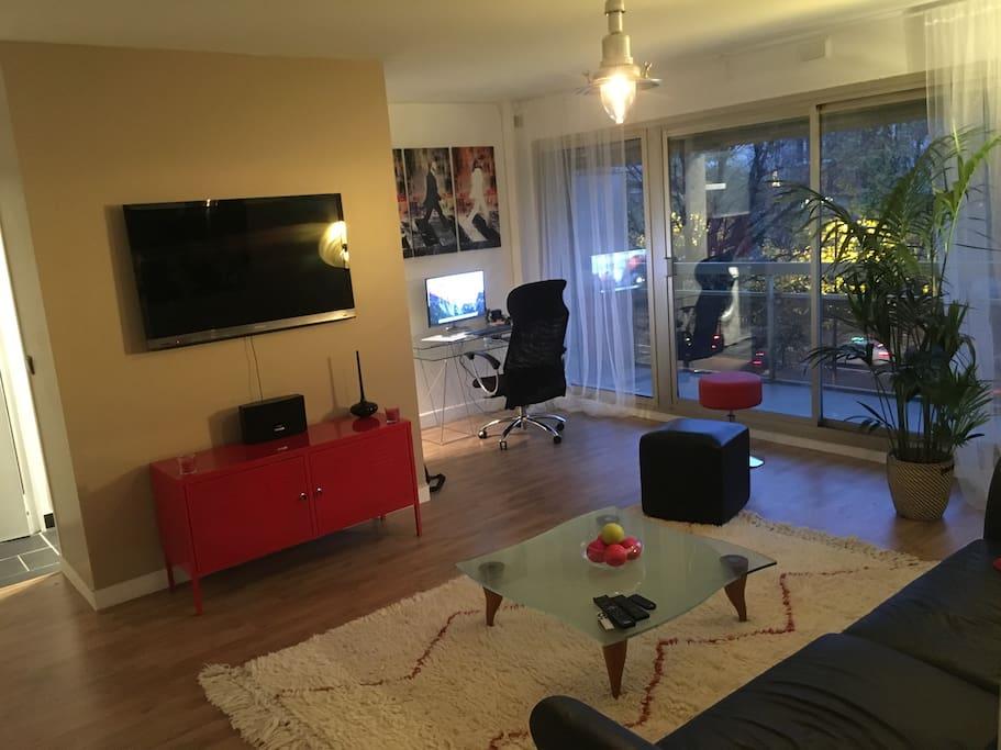 Grand living room avec canapé convertible, en lit deux places, télévision 120 cm, consoles de jeux (PS4, Wii U) et Apple TV et espace de travail et accès à la terrasse.