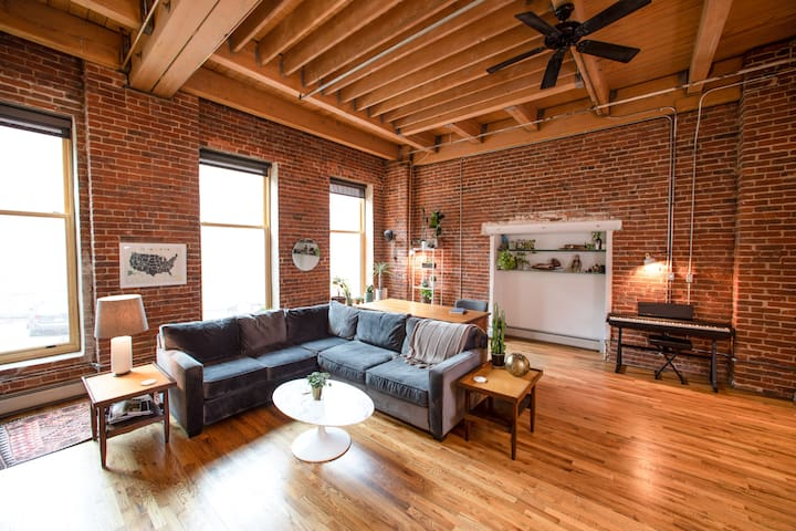 Exposed brick and ceiling beams give this loft charm and character. Relax in the living space, practice your piano skills, practice yoga, or use the work space to be productive.