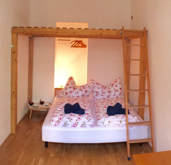 Bedroom with double bed and double bunk bed on top. Comfortable cushions and blankets.