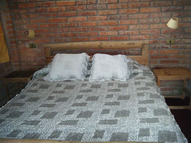 Double bed with bedside table and lights.