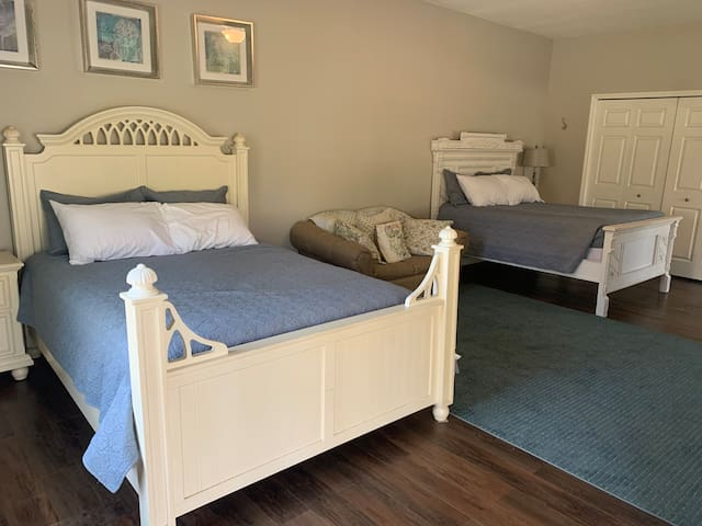 Bedroom of the listed space.  It is very large. One queen bed, one full bed, and a twin sleeper sofa. Television is also here-not seen in photo.  If you need an extra bedroom, it is at the other end of the kitchen and may be available upon request