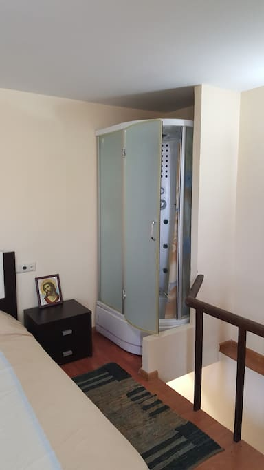 Bedroom with private shower cabin that has radio