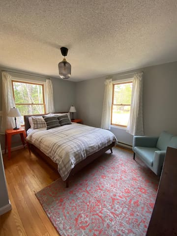 The master bedroom has a queen bed, reading chair, and double closet.