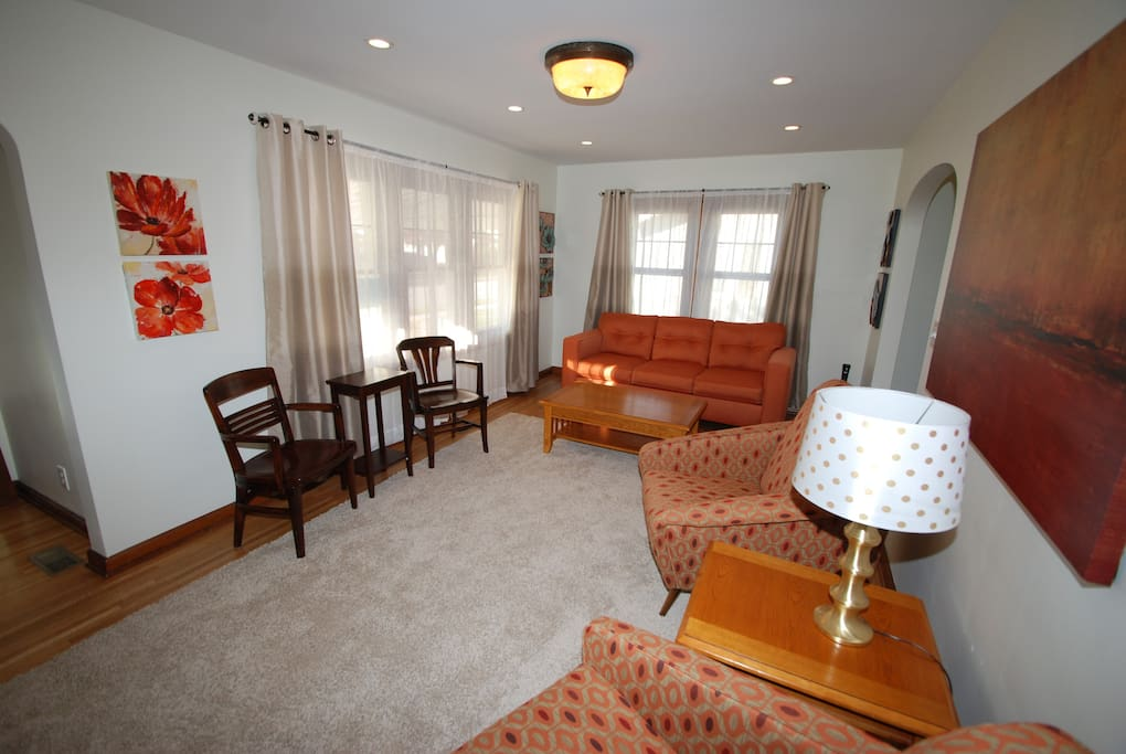 Comfortable living room with plenty of seating and natural light. TV on the wall and Q pullout couch.