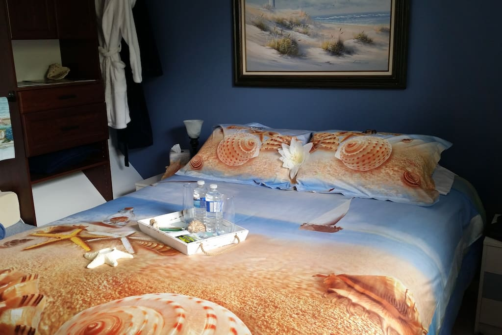 Beach themed Queen bed across from shared bathroom.
